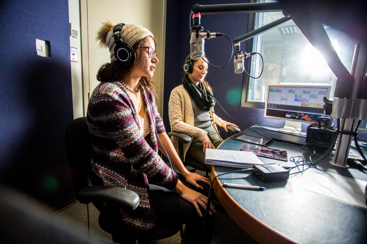 Two students sit at microphones in a radio studio reading the news